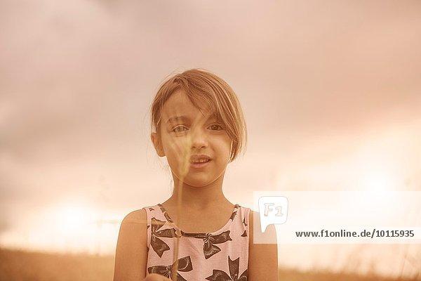 Porträt eines Mädchens mit Weizenähren vor dem Gesicht im Weizenfeld