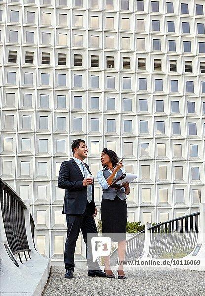 Geschäftsleute stehen und reden  halten Papierkram  zeigen und schauen nach oben.