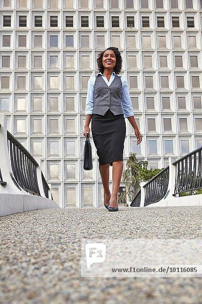 Vorderansicht der Geschäftsfrau beim Gehen  Tragen der Aktentasche  lächelnd  wegschauend