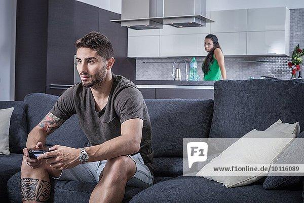 Junger Mann auf Sofa mit Spielkontrolle von wütender Freundin beobachtet
