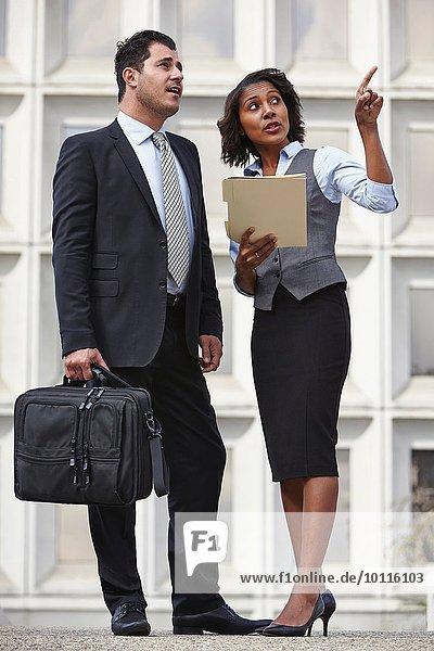 Gesamtansicht der Geschäftsleute  die sprechen  nach oben zeigen  nach oben schauen