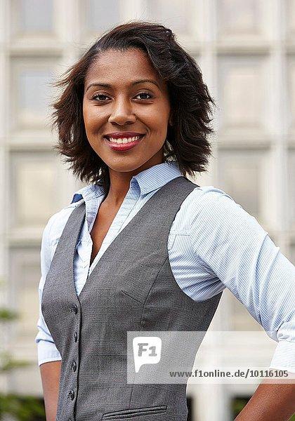 Porträt einer jungen Geschäftsfrau  mit Weste  Hände auf den Hüften  Blick in die Kamera  Lächeln