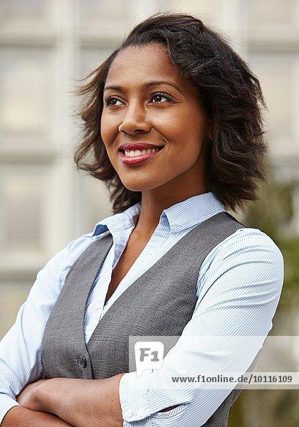 Porträt einer jungen Geschäftsfrau  die eine Weste trägt  wegschaut  die Arme gefaltet  lächelnd