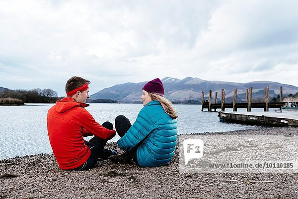 Young couple hiking  sitting by waters edge  Derwent Water  Keswick  Lake District  Cumbria  United Kingdom