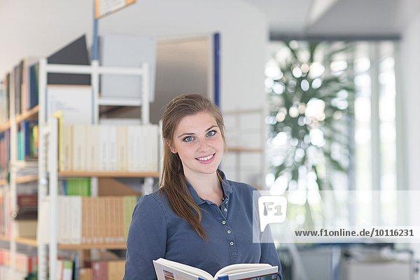 Porträt einer jungen Studentin in der Bibliothek