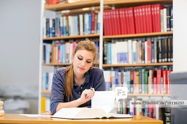 Young female student reading textbook at library desk