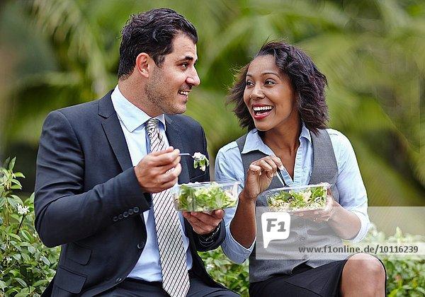 Geschäftsleute sitzen Seite an Seite und genießen einen Salat in der Mittagspause  von Angesicht zu Angesicht  lächelnd....
