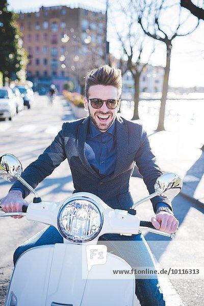 Porträt eines lächelnden jungen Mannes  der auf einem Moped am Straßenrand sitzt.