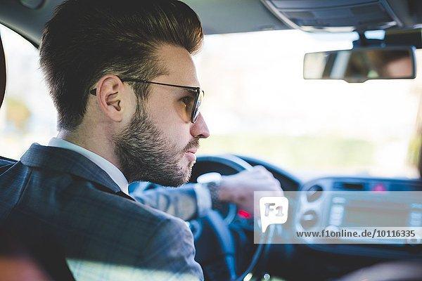 Rückansicht des jungen Geschäftsmannes beim Autofahren