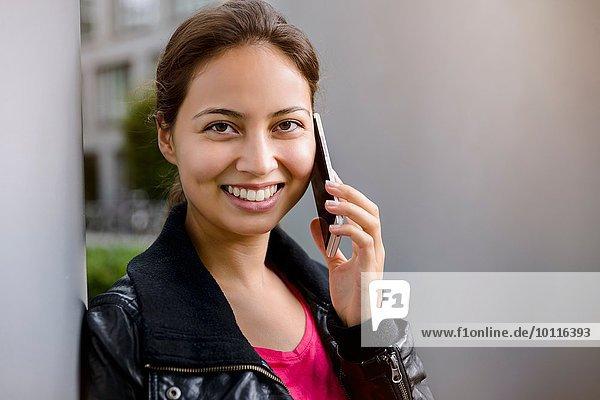 Portrait einer jungen Frau  die sich gegen die Säule lehnt und auf dem Smartphone spricht.
