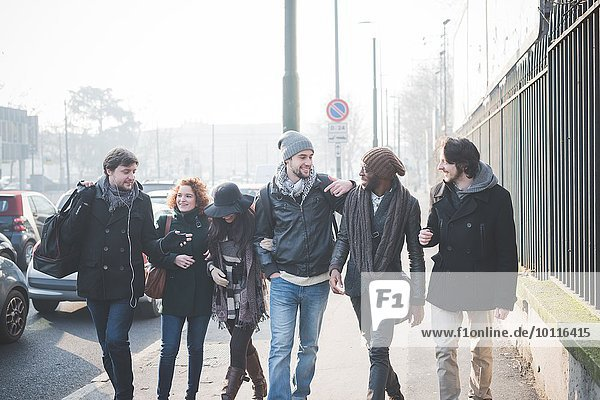Sechs junge erwachsene Freunde plaudern beim Spaziergang durch die Stadt.