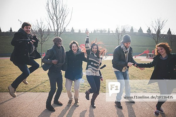 Six young adult friends dancing and jumping in park