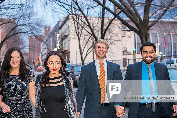 Portrait of four smartly dressed young adult friends walking along street