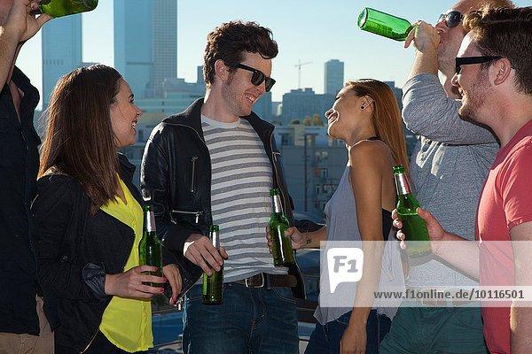 Sechs erwachsene Freunde flirten und tranken Bier an der Dachbar mit der Skyline von Los Angeles  USA.