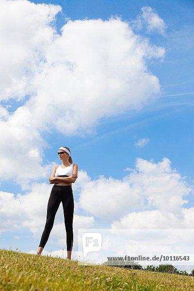 Portrait des Joggers gegen den blauen Himmel der Landschaft