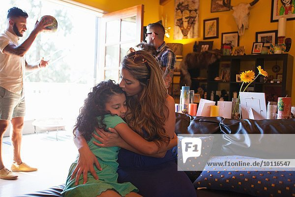 Woman hugging and kissing daughter in living room