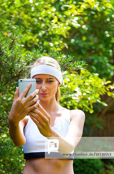 Frau trägt ein Sport-Top und nimmt sich selbst im Garten.