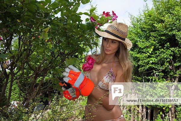 Frau mit Bikini-Baumschnitt im Garten