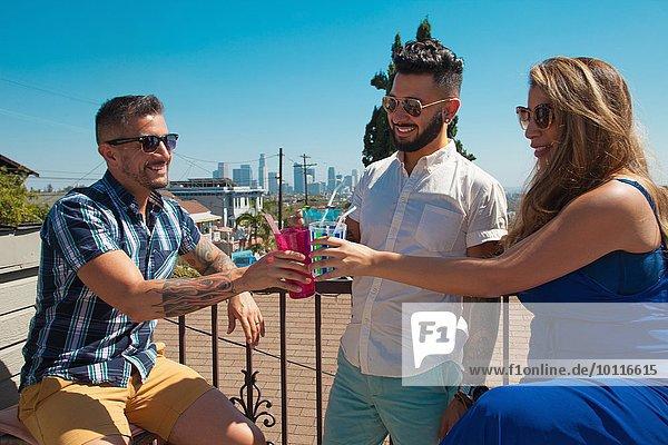 Frau und zwei erwachsene Brüder stoßen mit Cocktails auf der Terrasse an.