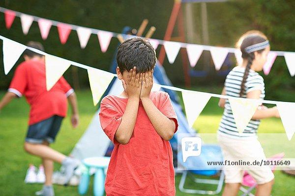 Junge  der seine Augen zum Verstecken mit Geschwistern im Garten verschließt