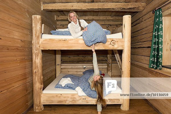 Two young women friends fooling around with pillows on bunk beds in log cabin