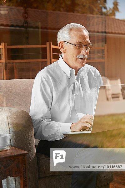 Senior Mann zu Hause  mit Laptop