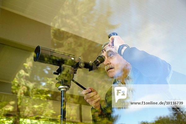 Senior Mann zu Hause  mit Teleskop durchs Fenster