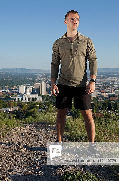 Portrait of young male runner on dirt track above city in valley