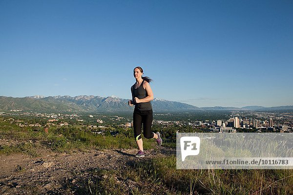 Young female runner running along track above city in valley