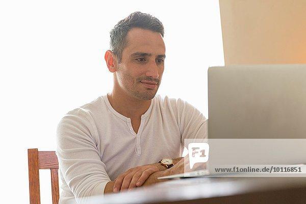 Mittlerer Erwachsener Mann am Schreibtisch sitzend  mit Laptop