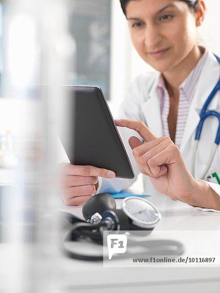 Ärztin mit digitaler Tablette zur Aktualisierung von Krankenakten