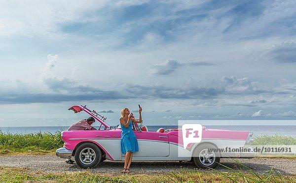 Junger Mann versucht  ein altes Cabriolet an der Küste zu reparieren  während die Freundin sich schminkt  Havanna  Kuba