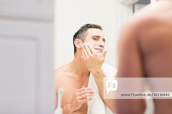 Mittlerer erwachsener Mann  Blick in den Spiegel  Rasierschaum im Gesicht  Rückansicht