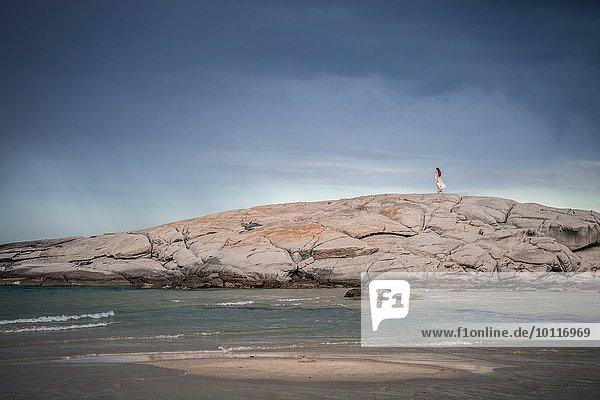 Fernsicht einer jungen Frau  die auf Felsformationen an der Küste  Costa Rei  Sardinien  Italien schlendert.