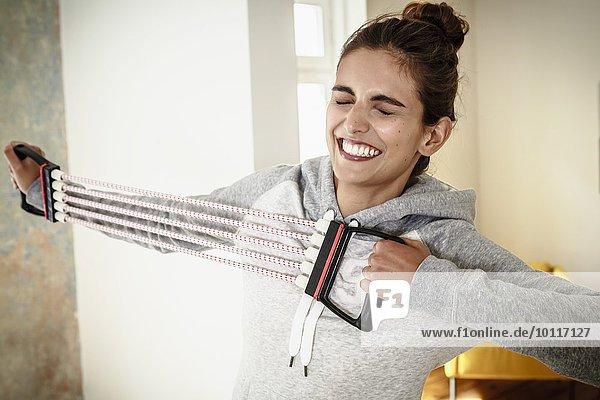 Junge Frau  die sich anstrengt  mit einem Brust-Expander im Wohnzimmer zu trainieren.