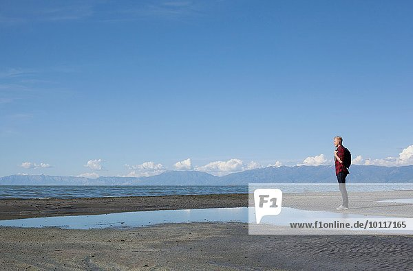 Side view of young man standing at waters edge looking out  Great Salt lake  Utah  USA