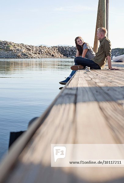 Side view of young couple sitting on wooden pier talking  Great Salt Lake  Utah  USA