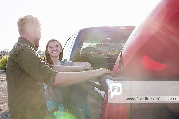 Young couple leaning against pick up truck  looking at each other smiling  lens flare