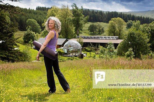 Porträt einer reifen Frau mit Yogamatte im Feld der Öko-Lodge