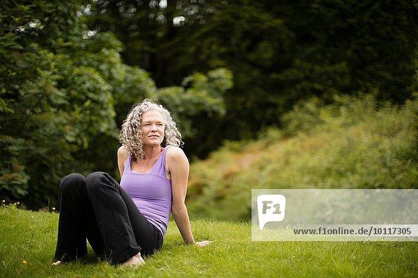 Reife Frau  die eine Pause von der Yogapraxis im Feld macht.