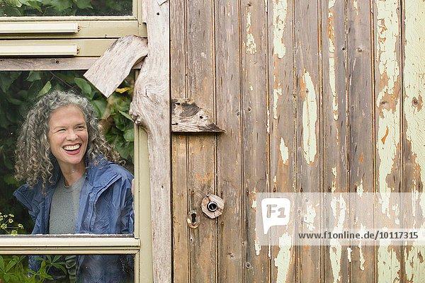 Lächelnde reife Frau schaut aus dem Gewächshausfenster