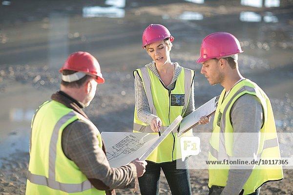 Architekt und Bauherren  die auf die Bauplanung auf der Baustelle verweisen