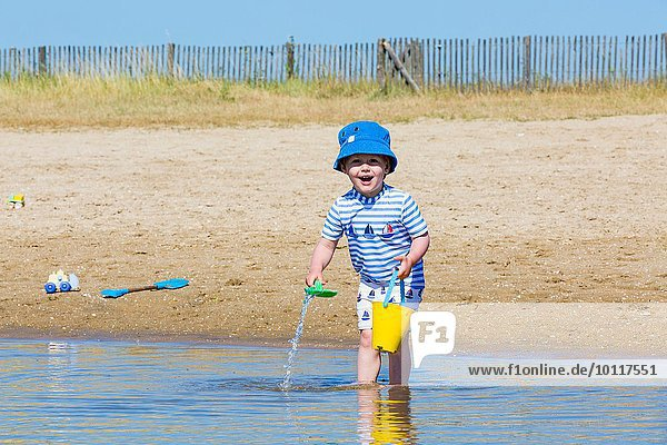 Portrait of small boy collecting seawater in toy bucket at beach  Marennes  Charente-Maritime  France
