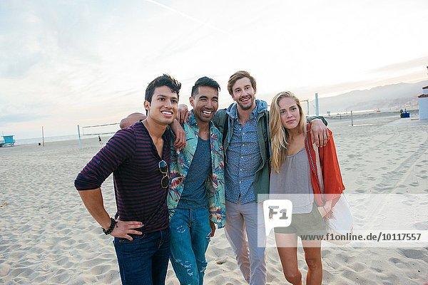 Gruppe von Freunden  die zusammen am Strand stehen und lachen.