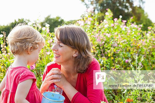 Mid adult mother and toddler daughter in flower field