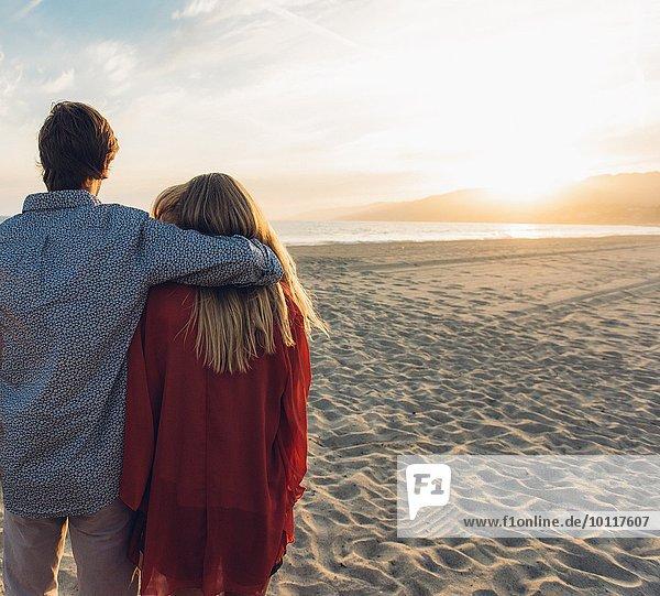 Junges Paar am Strand stehend  umarmend  Rückansicht