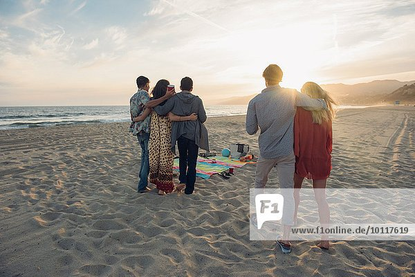 Group of friends standing on beach  hugging  rear view