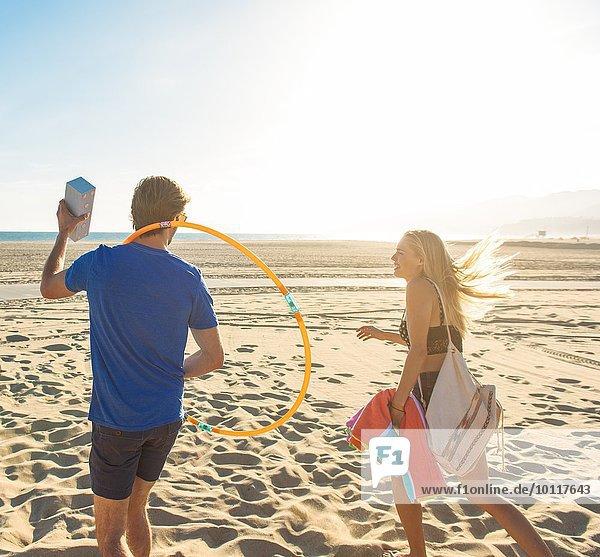 Junges Paar beim Spaziergang am Strand  Rückansicht