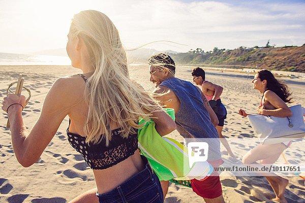 Gruppe von Freunden  die am Strand laufen  Rückansicht