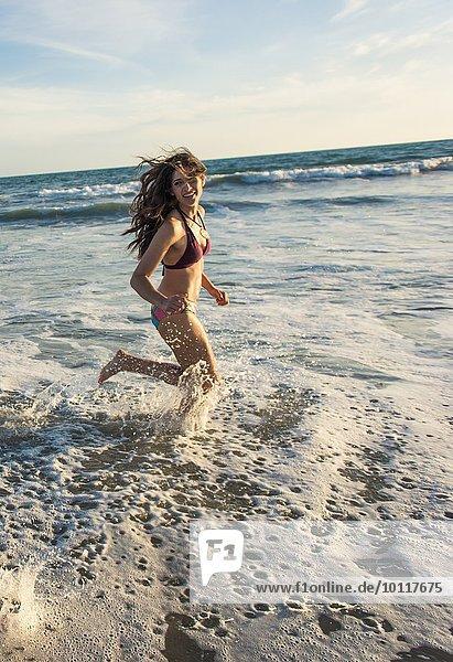 Junge Frau  die im Meer läuft